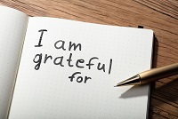 """I am grateful for"" written in a notebook with a pen."